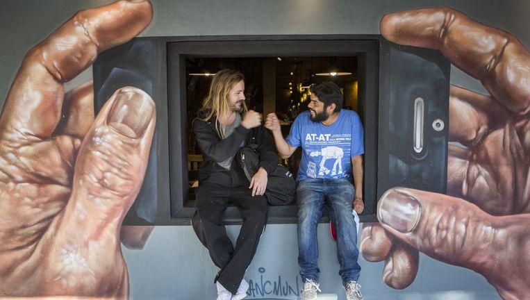 Alejandro Revilla (rechts) en Jenaro de Rosenzweig 'in' een van de muurschilderingen in Mexico-Stad. Ze begonnen met een digitale inventarisatie van muurkunst in de stad, maar al snel kregen ze opdrachten en gingen ze bemiddelen tussen bedrijven en kunstenaars. Beeld Julius Schrank / de Voklskrant