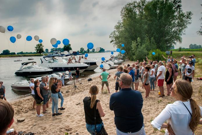 Ballonnen worden opgelaten op het strandje aan de Maas tijdens de herdenking van de bij een jetski-ongeluk omgekomen 14-jarige Levi Thoonen uit Helmond