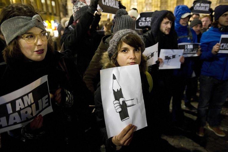 Deelnemers aan een demonstratie op de Dam voor de persvrijheid, naar aanleiding van de aanslag op de redactie van het Franse satirische weekblad Charlie Hebdo waarbij twaalf doden vielen. Beeld anp