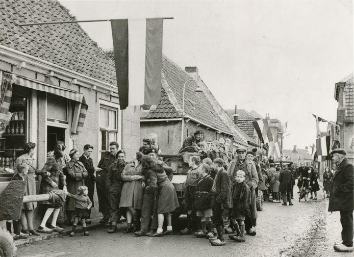 Wolphaartsdijk, 30 oktober 1944: Bevrijding van Wolphaartsdijk. De bevolking verwelkomt de Canadezen in de Dorpsstraat - nu Kerkstraat. Het blijkt dat veel Zeeuwen een Nederlandse vlag op zolder hebben liggen. Foto Beeldbank WO2, NIOD