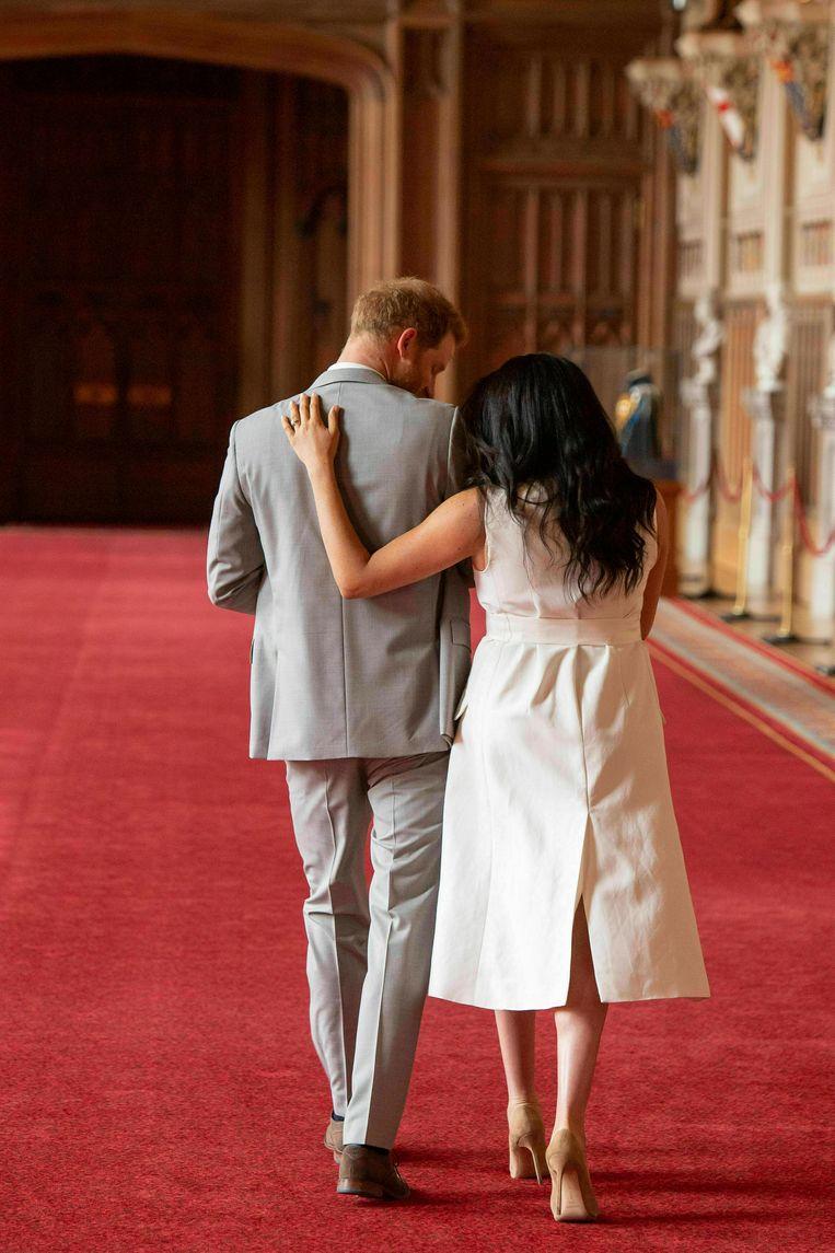 Harry en Meghan lopen weg na het tonen van hun pasgeboren zoontje.