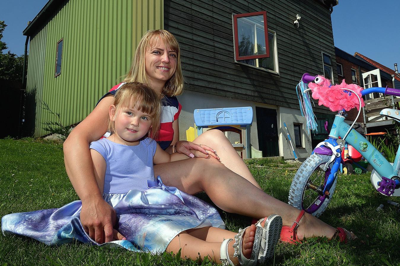 De Hongaars-Roemeense Piroska Papp (34) met dochter Helen in de tuin van haar dijkhuisje in Dinteloord.