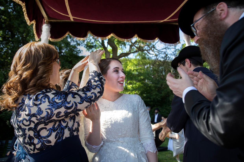 Aan het einde van de ceremonie haalt moeder de sluier van haar pasgetrouwde dochter weg. Rechts de vader van de bruid.
