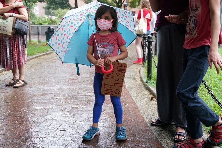 Een kind bij een betoging in New York tegen de heropening van scholen voordat de veiligheid is op orde is.  Beeld Carlo Allegri / Reuters