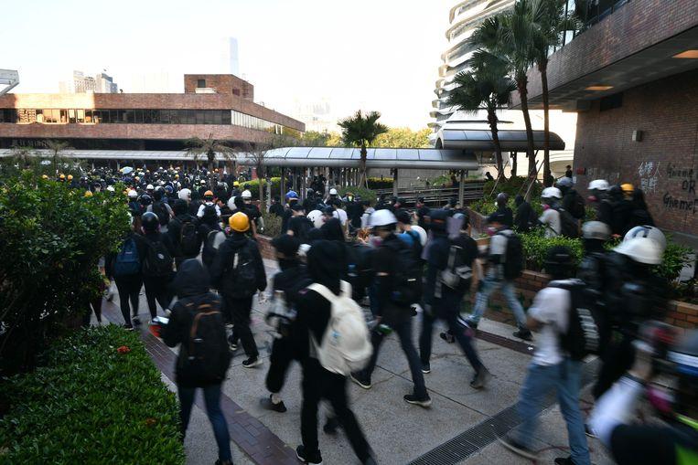 Een grote groep studenten verlaat de campus.