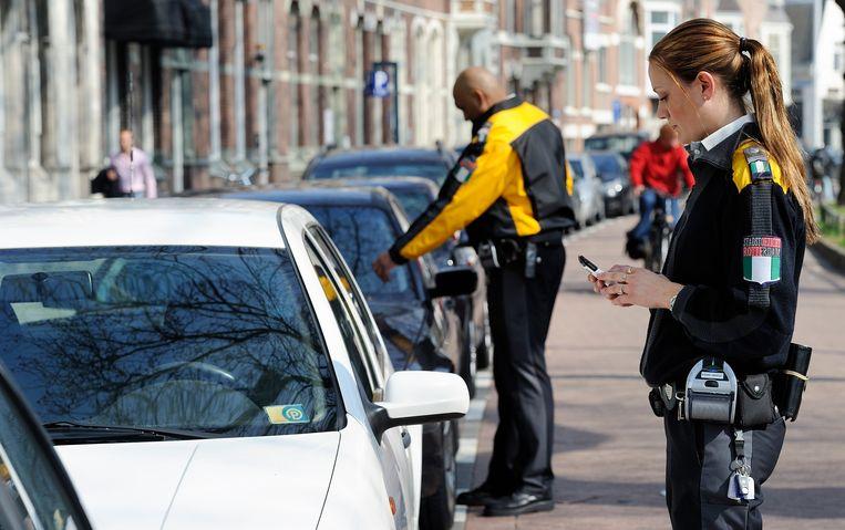 Stadswachten in Rotterdam controleren geparkeerde auto's.  Beeld ANP XTRA