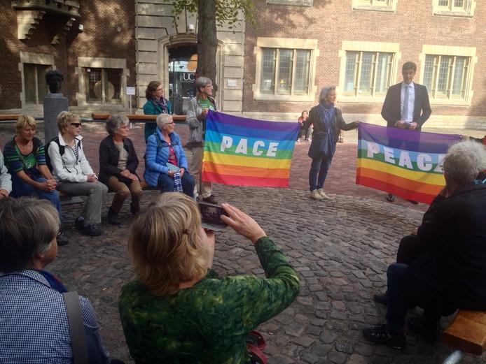Wethouder Chris Dekker spreekt de deelnemers aan de eerste Walk of Peace in Middelburg toe in het Metamorfose Lokaal van UCR op de Helm.