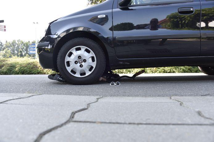 Bij een aanrijding tussen een personenauto en een fietser, kwam de fiets onder de auto klem te zitten.