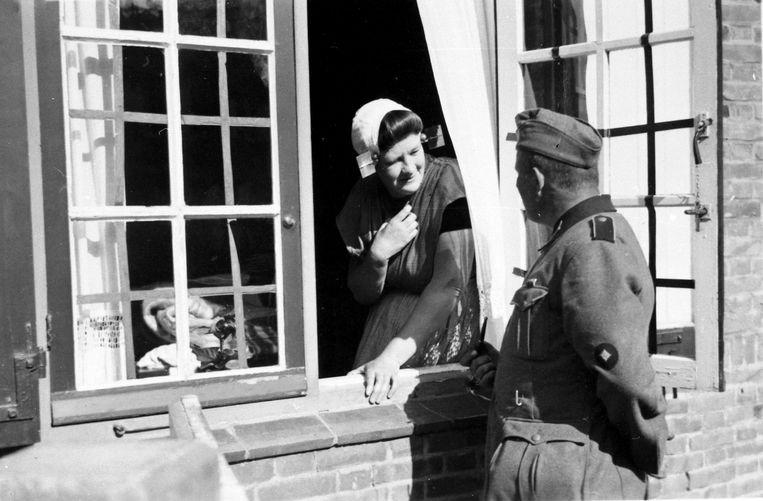 Propagandabeeld: Vrouw in Zeeuwse klederdracht maakt een praatje met Duitse soldaat, Goes, 1940. Beeld Zeeuwse Bibliotheek