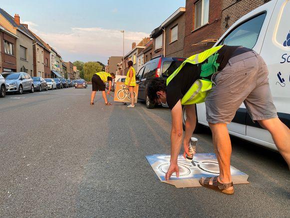 Vrijwilligers van het GMF schilderen fietsicoontjes in de Kapiteinstraat in Wondelgem