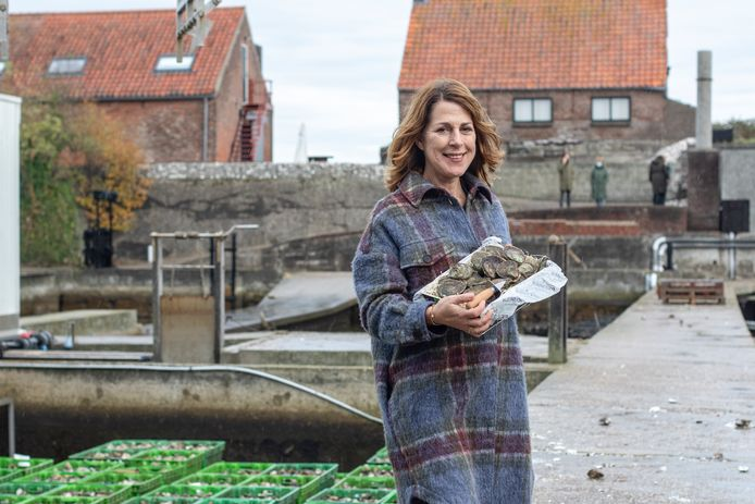 Caroline Verwijs bij de oesterputten met een doosje platte Heritage-oesters, een merk dat is gelanceerd om het 140-jarig bestaan te vieren.