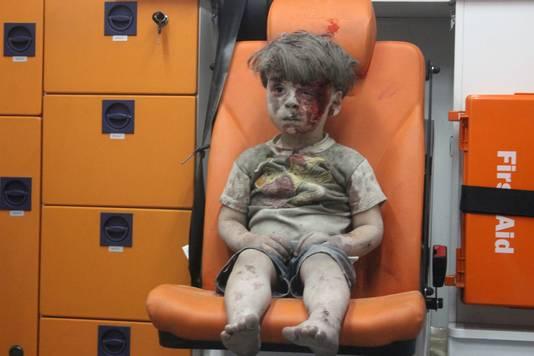 Omran zit versuft en onder het bloed en stof in de ambulance.
