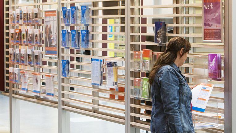 Een werkzoekende bekijkt vacatures bij een vestiging van UWV Werkbedrijf in Rotterdam. Beeld ANP