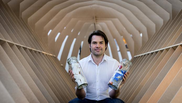 Marius Smit staat in het karkas van een boot die gemaakt gaat worden van plastic afval afkomstig uit de Amsterdamse grachten. In zijn handen houdt hij het plastic (R) en het eindproduct waar de boot van gemaakt gaat worden.