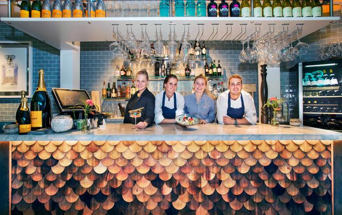 Medewerkers Gina, Monica, Claire en Mitch (v.l.n.r.) achter de bijzondere bar met schubben.