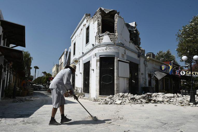 Een man ruimt puin voor zijn bar na de aardbeving eind juli.