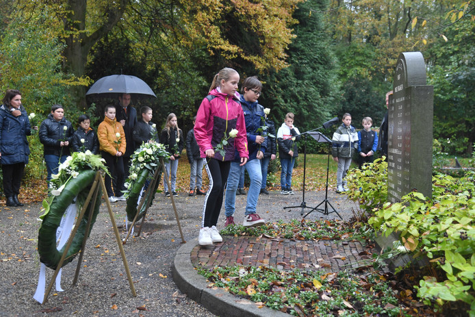 Vlinder en X Paul Bergmans uit groep 8 van basisschool De Palmenhof leggen rozen bij het oorlogsmonument op de begraafplaats in Sint Laurens tijdens de herdenking van 75 jaar bevrijding.
