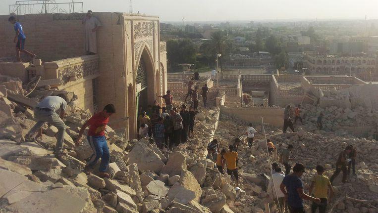 Mensen lopen door de puinhopen van de eeuwenoude Moskee van de profeet Jonah die door IS is vernield omdat er afgoderij zou plaatsvinden. Het verhaal van Jonah die wordt opgeslokt door een walvis komt in zowel de bijbel als de koran voor. Beeld ap