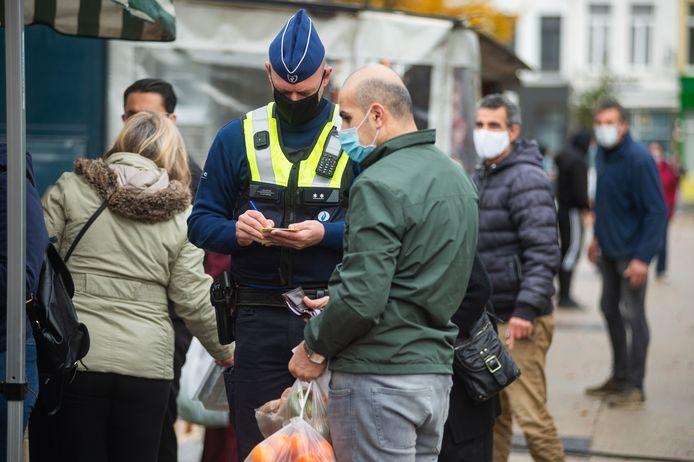 De politie beboet een passant op de wekelijkse markt op het Sint-Jansplein. De man droeg zijn mondmasker niet consequent.