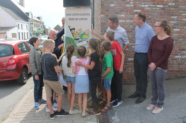 In het bijzijn van burgemeester Kris Poelaert en enkele leerlingen onthult de komiek het verkeersbord aan De Regenboog.