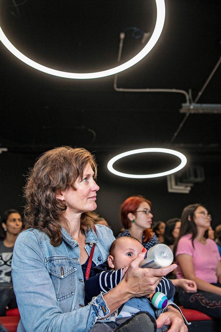 Een vrouw geeft haar baby de fles tijdens een lezing op de open dag van Codam. Beeld