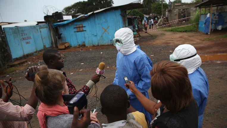 Een arts van een Liberiaans ebola-centrum spreekt met journalisten. Een staking onder medisch personeel in Liberia voor een hogere risicovergoeding kon gisteren worden afgewend. Veel verpleegkundigen zeiden het niet met hun geweten in overeenstemming te kunnen brengen om hun vaak doodzieke patiënten niet te verzorgen. Beeld Getty Images