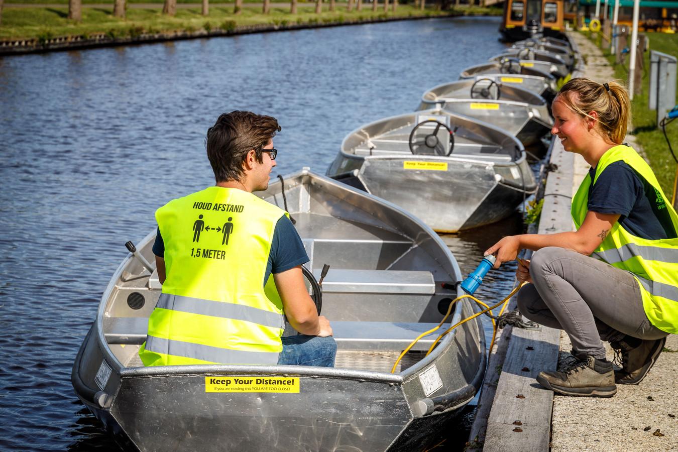 Jordi en Marloes van de Arendshorst bij één van de fluisterbootjes die klaar liggen voor gebruik. Met hun hesjes en de bumpersticker hopen ze de anderhalvemeter-restricties te kunnen waarborgen.