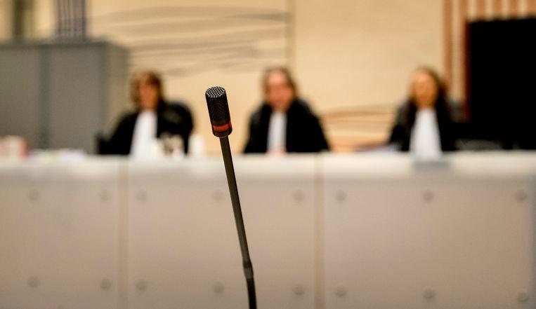 Een microfoon met op de achtergrond rechters (VLNR) S. Pompe, B. Vogel en J. Oreel voor aanvang van de behandeling van de vordering tot herroeping van de voorwaardelijke invrijheidstelling van Volkert van der G. in 2017. Beeld Anp