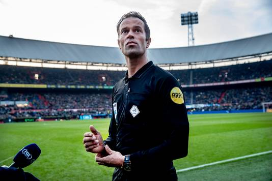 Scheidsrechter Bas Nijhuis kijkt onheilspellend naar de lichtmasten die het niet doen.