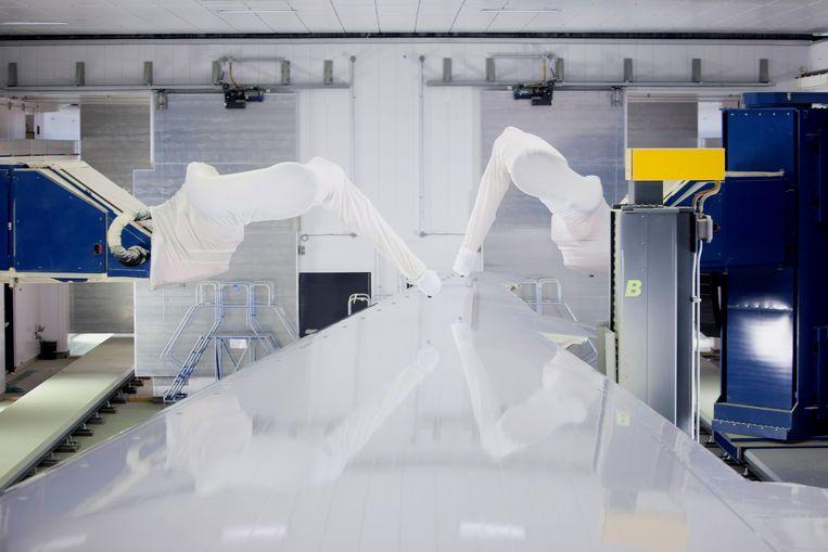 Robots spuiten verf op een vleugelonderdeel. Beeld Getty