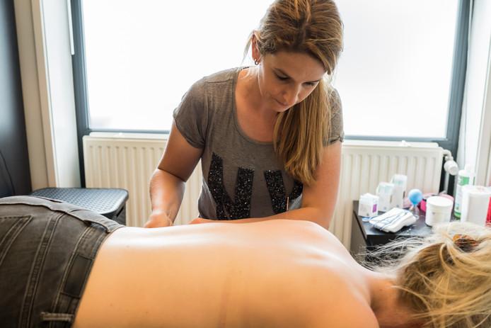 Fysiotherepeut Jill Bomers met een patiënt op de behandeltafel.
