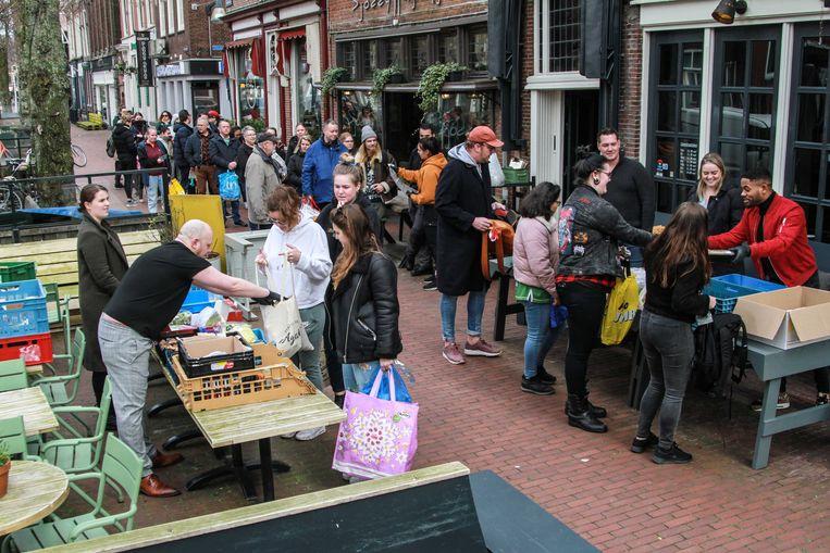 Drukte bij eetcafé het Leven aan de Tweebaksmarkt in Leeuwarden. Het restaurant gaf alle verse producten weg aan minder bedeelden nadat er strenge coronamaatregelen werden aangekondigd.  Beeld Anton Kappers / ANP