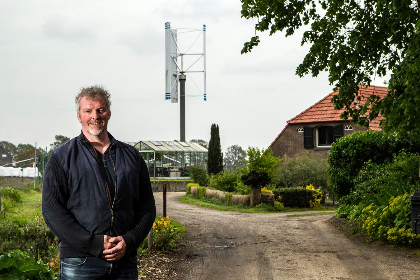 Jacco Korenblik met op de achtergrond de windturbine die op zijn erf in het buitengebied van Harfsen staat.