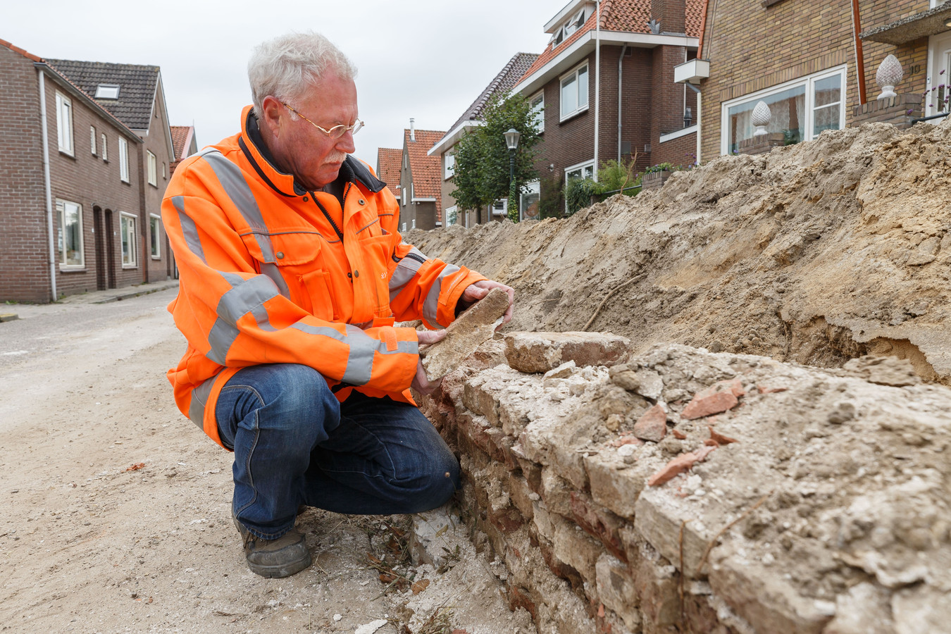 John Assink bij de restanten van de in de bodem gevonden stadsmuur langs het Justitiebastion