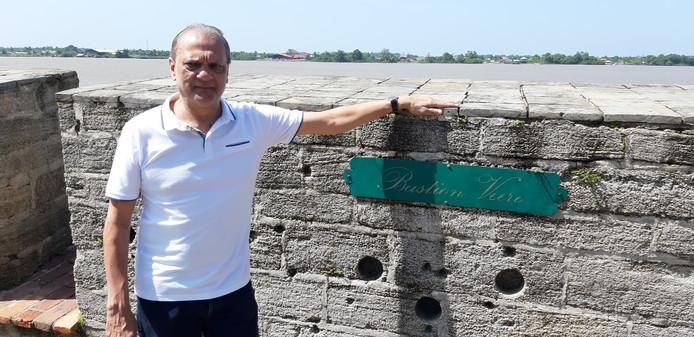 Sunil Oemrawsingh bij kogelgaten in de muur van Fort Zeelandia, waar de slachtoffers op 8 december 1982 werden geëxecuteerd