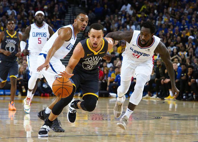 Warriors-guard Stephen Curry (m) in actie tegen LA Clippers.