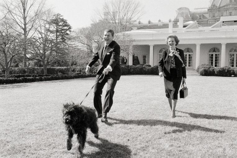 De hond Lucky van de voormalige Amerikaanse president Reagan gaat in 1985 met hem aan de haal in de tuin van het Witte Huis. Naast hem de toenmalige Britse premier Thatcher.  Beeld getty