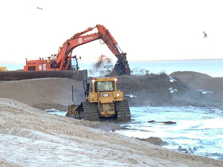 Bulldozers nivelleren de opgespoten zandhopen.