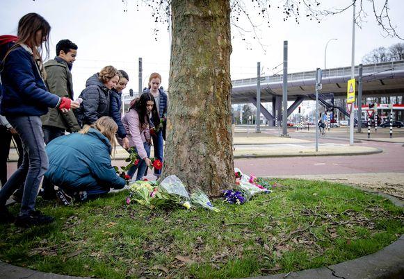Kinderen leggen bloemen neer vlak bij de tramhalte waar Gökmen Tanis (37) het vuur opende.