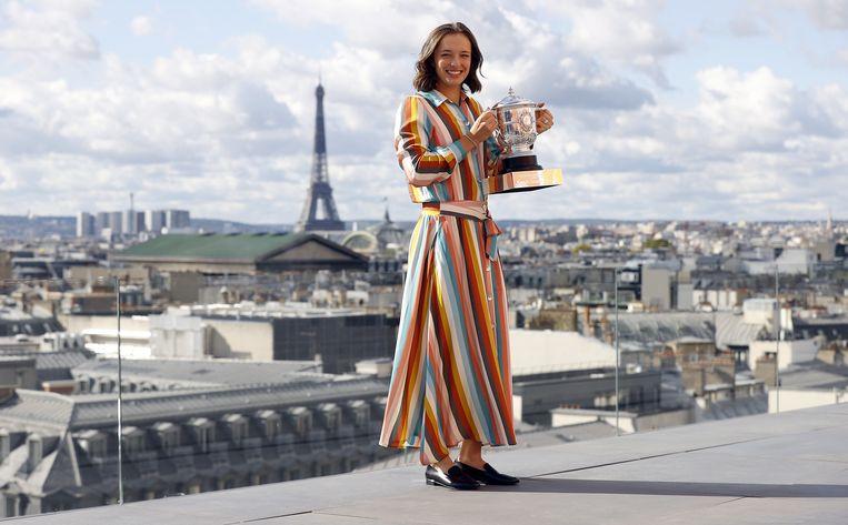 Iga Swiatek poseert met de trofee in Parijs. Beeld EPA