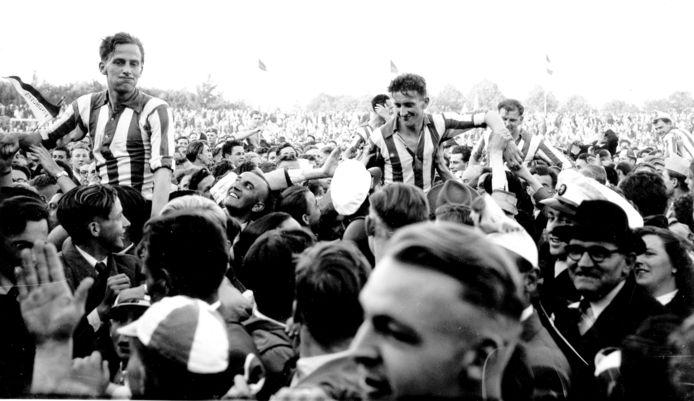 De foto is gemaakt na het behalen van het landskampioenschap tegen DOS in 1954. De spelers op de schouders zijn v.l.n.r. Willy Schmidt, Noud van Melis, achter hem met een hand op het oor, Cor Vlemmix en Frans van Tuijl en Frans Tebak