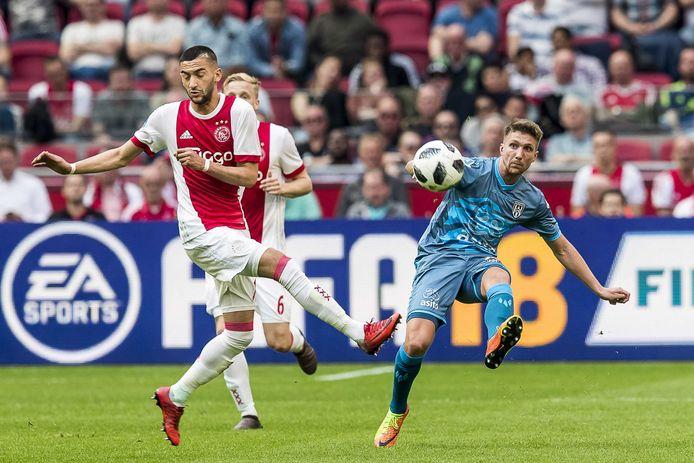 Peter van Ooijen namens Heracles Almelo in duel met Ajacied Hakim Ziyech.