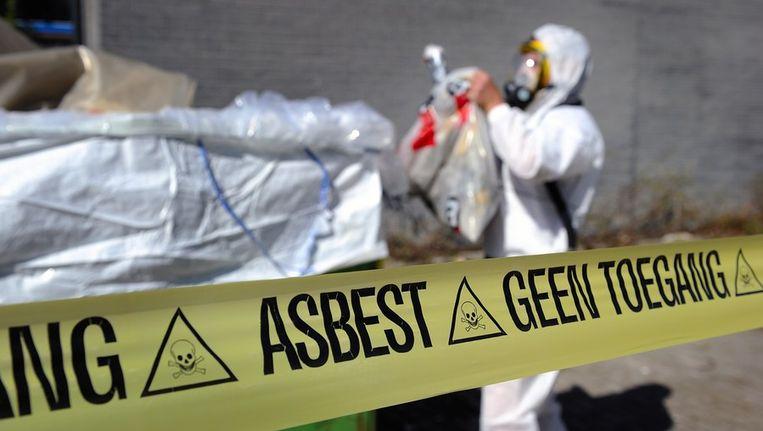 Een medewerker van een asbestsaneringsbedrijf verwijdert asbest. Beeld anp