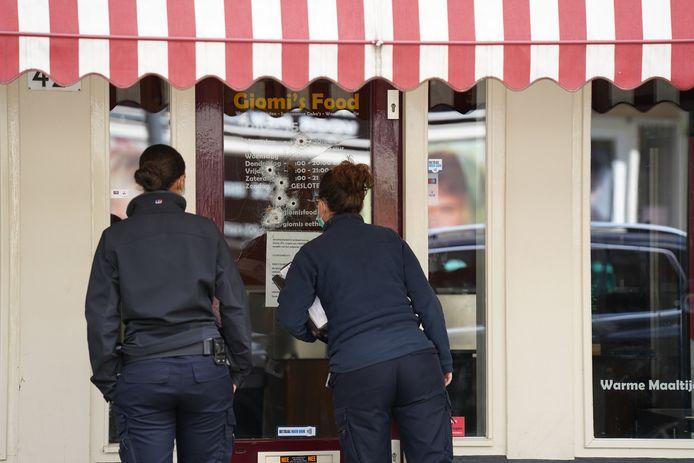 Rechercheurs van de forensische opsporing bekijken de kogelgaten in de deur van de boordjeszaak.