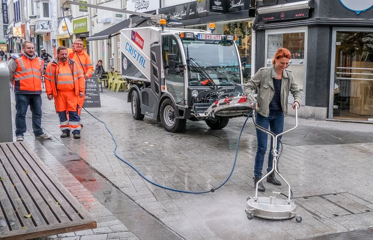 De machine heeft ook een handkoepel met roterende sproeiers. Schepen Ruth Vandenberghe probeerde die donderdagochtend even uit, op de hoek van de Lange en Korte Steenstraat.