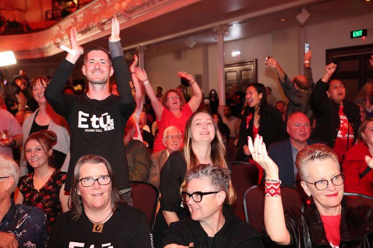 Aanhangers van de partij van Ardern bekijken de resultaten van de verkiezingen. Met meer dan de helft van de stemmen geteld gaat haar partij Labour op kop met 50 procent van de stemmen. Beeld AFP