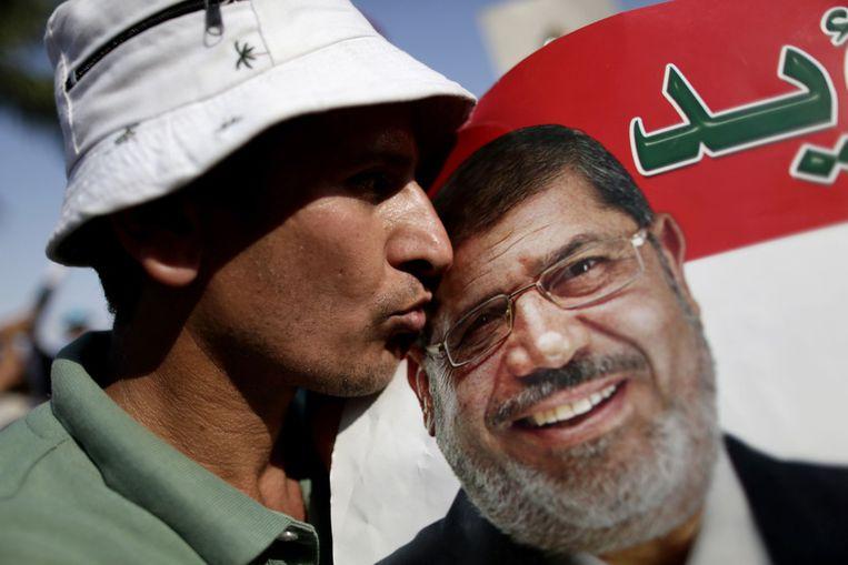 Een aanhanger van Morsi kust een portret van de president. Beeld null