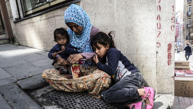 Een vrouw met haar twee kinderen bedelt in Istanbul, Turkije. Beeld AFP