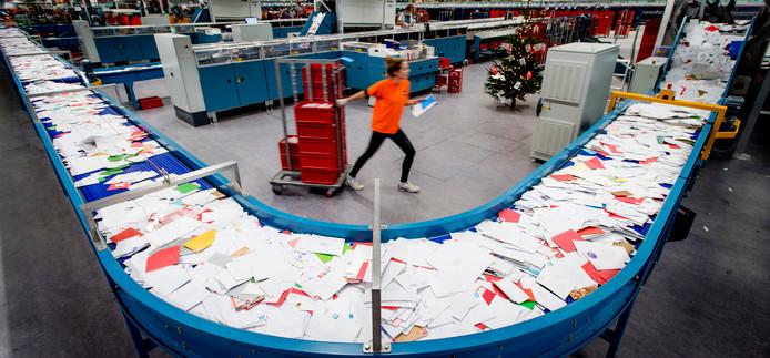 Drukte in een brievensorteercentrum van PostNL. Voortaan maakt het postbedrijf een strikt onderscheid tussen brieven en goederen.