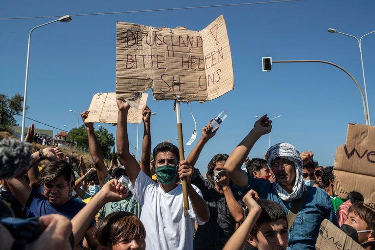 Migraten op Lesbos met borden waarop in het Duits staat geschreven 'Duitsland help ons'.  Beeld AP